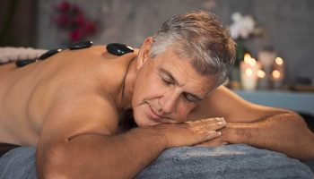 Mature man relaxing on bed during hot stone massage. Portrait of senior man with closed eyes resting during lastone therapy. Handsome man with black lava stone on back at spa with candles in background.